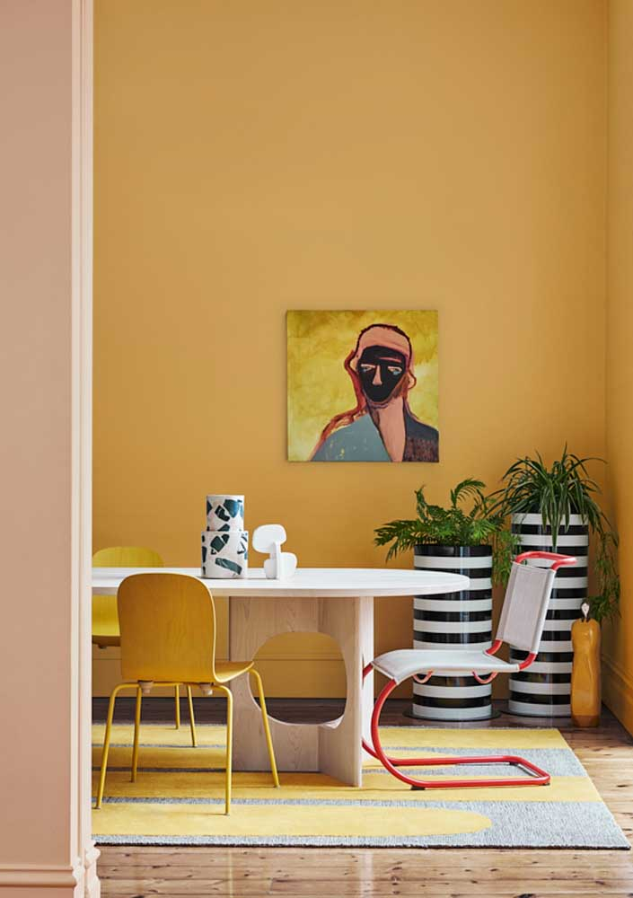Warm and full of energy, this room impresses with the dramatic use of yellow that covers the entire wall and still colors the carpet and chairs
