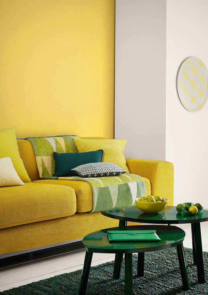 Yellow wall and sofa to create a visual ensemble. Green tones ensure freshness for the room