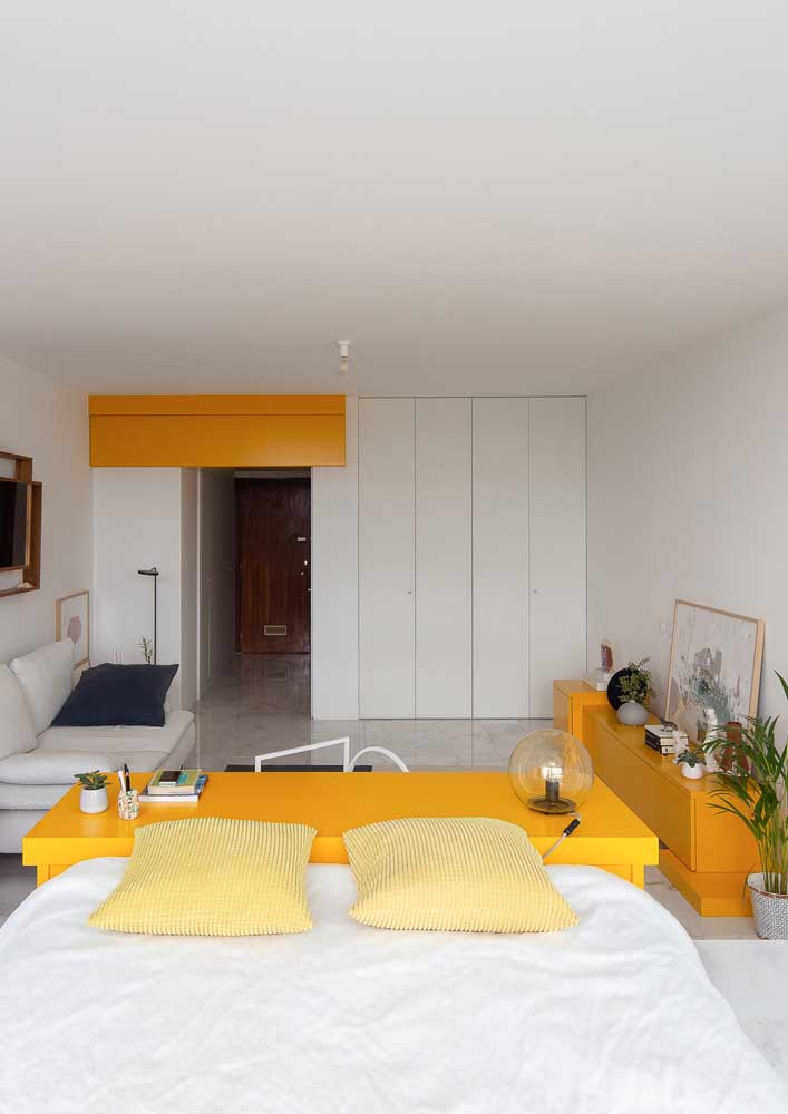 This large and modern room bet on the use of white as a background for the yellow details