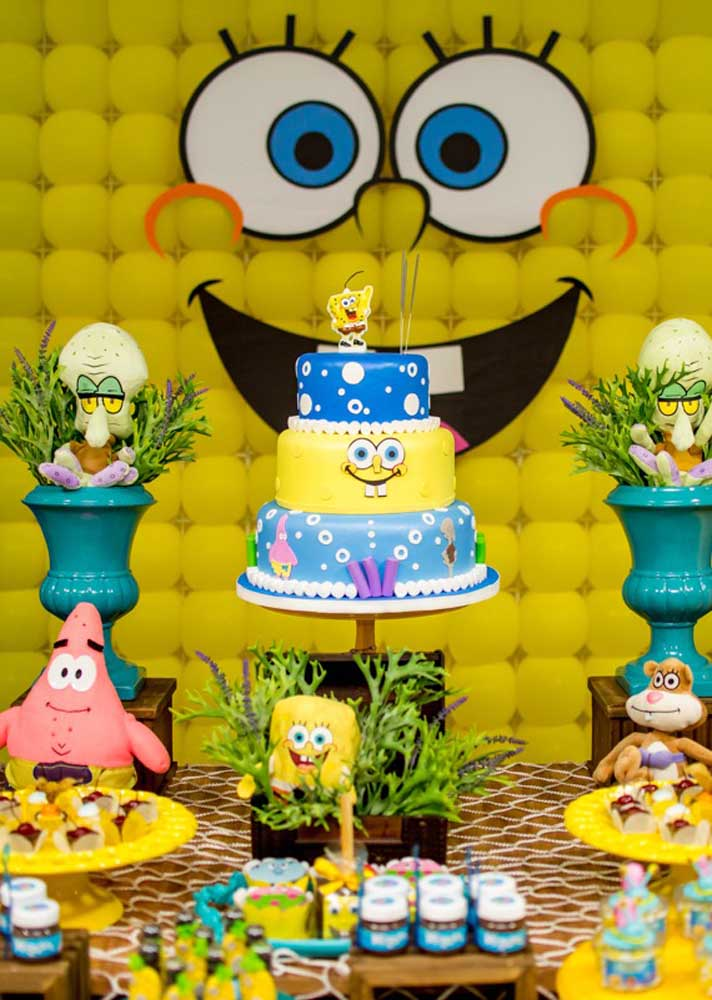 Table decorated with SpongeBob cake. Right behind, a relaxed panel of balloons shapes the main character