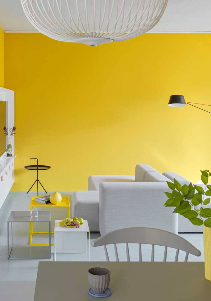 Yellow and white room with gray accents. Natural lighting brings even more coziness to decor