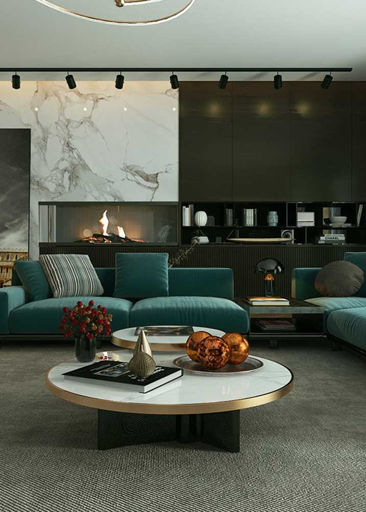 Living room with green sofa. To match, gray carpet and black wall with marble cladding