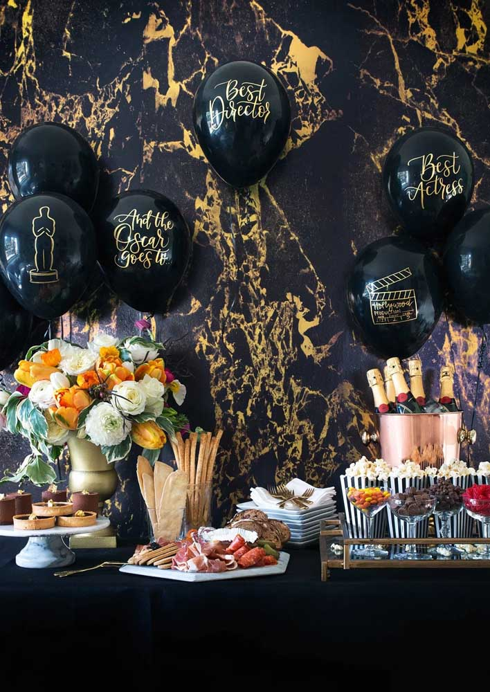 A super decorating idea for the movie night: black and gold showered with colorful flowers. On the wall, balloons with nominations for the best Oscar categories