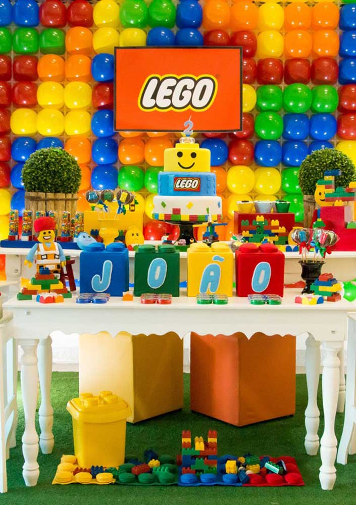 Cake table decorated with Lego theme. Notice that the panel at the back was made with balloons imitating the toy pieces