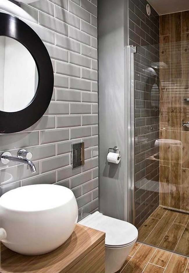 Gray, black and wood make up the decor of this small decorated bathroom