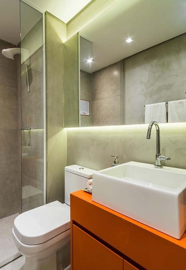 The orange cabinet gives color and life to the sober-colored bathroom