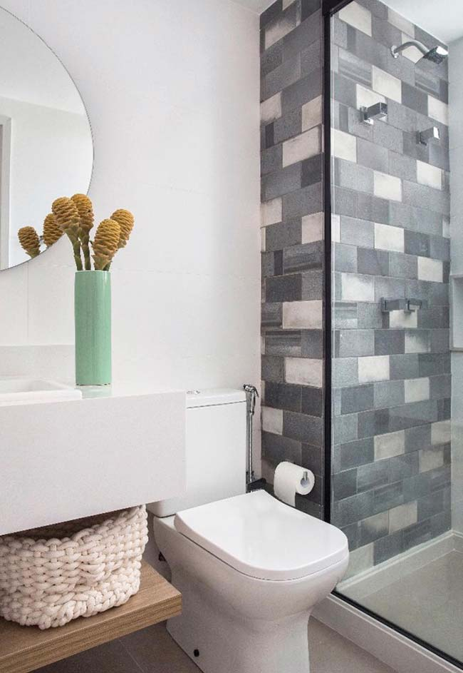Box of blue and gray tiles contrasts harmoniously with the rest of the white bathroom