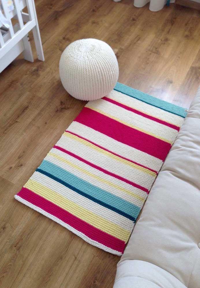 As listras coloridas quebram a brancura do tapete simples de crochê