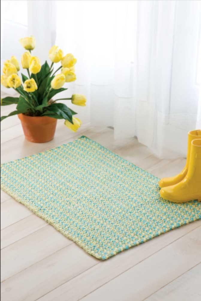 O amarelo discreto do tapete de crochê simples forma um dialogo leve e sutil com os acessórios de decoração