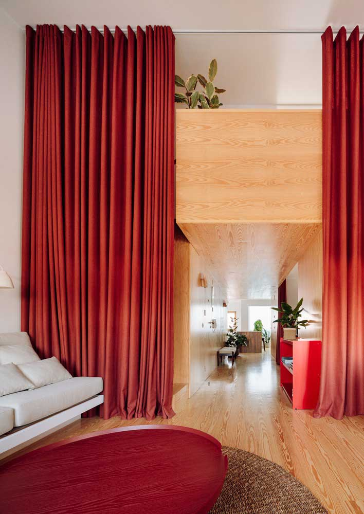 Room with red curtain that doubles as room divider