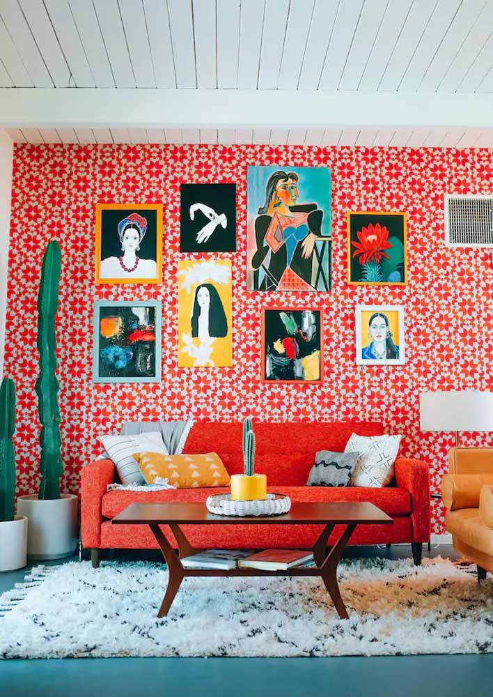 Room with super relaxed red wall. The paintings make the decoration even more complete