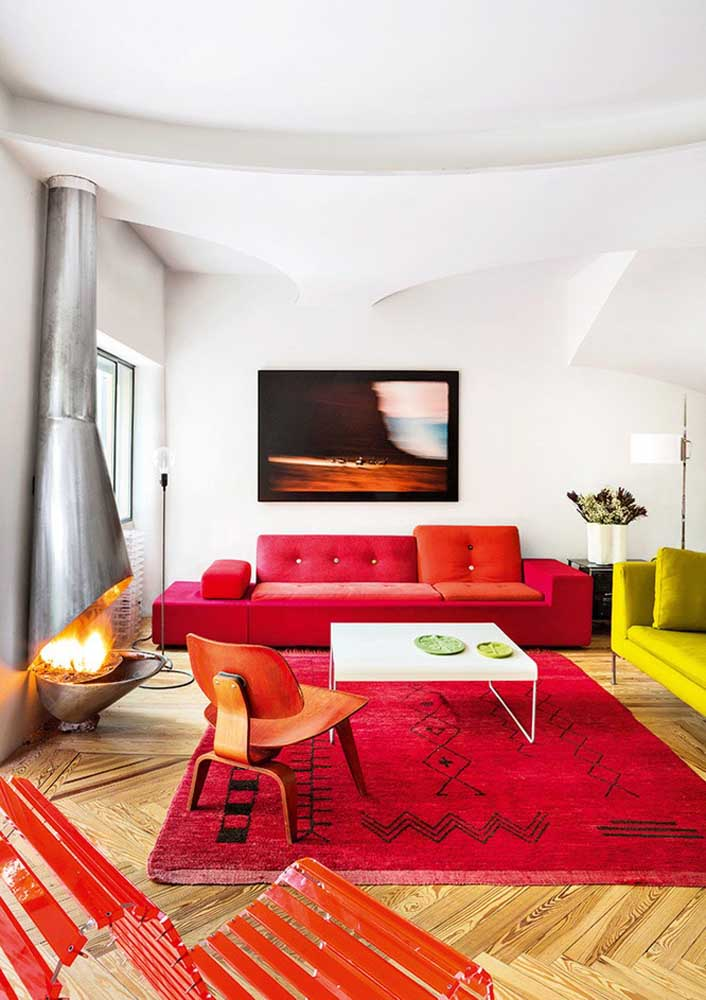 Red sofa, carpet and armchairs stand out in this white-walled room. The lemon yellow sofa makes the counterpoint in the decoration