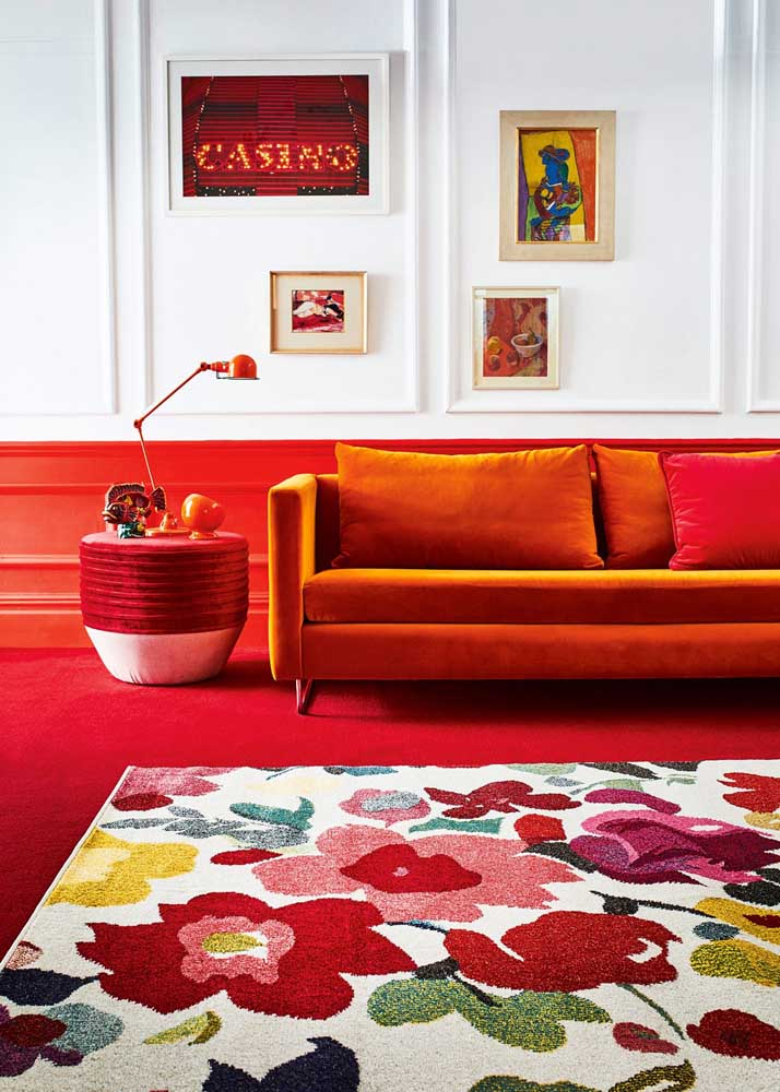 A classic room decorated with a floor and half a red wall. Red still appears in a punctual way on the carpet, sofa, lamp and pictures