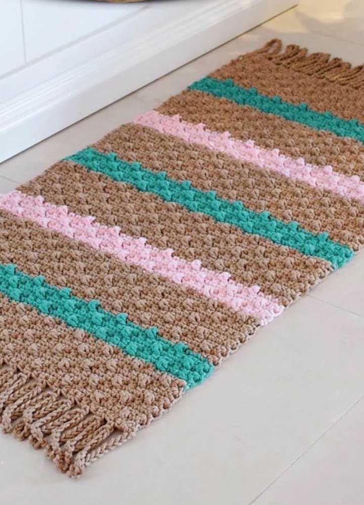 Para decorar o hall de entrada, um modelo de tapete de crochê simples com franjas e em três cores diferentes