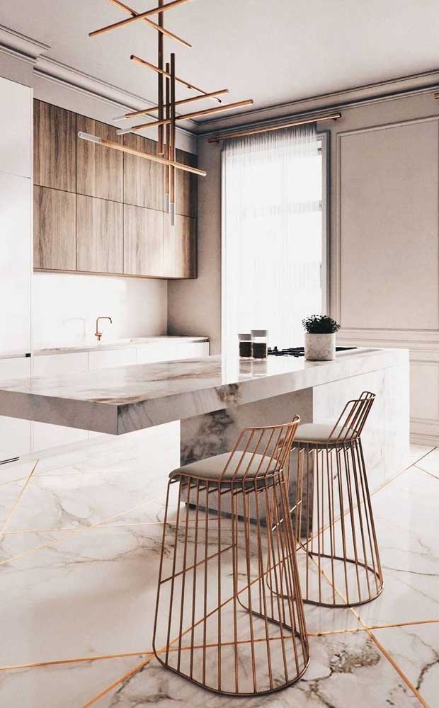 Modern and sophisticated cuisine in shades of white and ivory combined with the golden metallic tone of the stools and the elegant texture of the marble