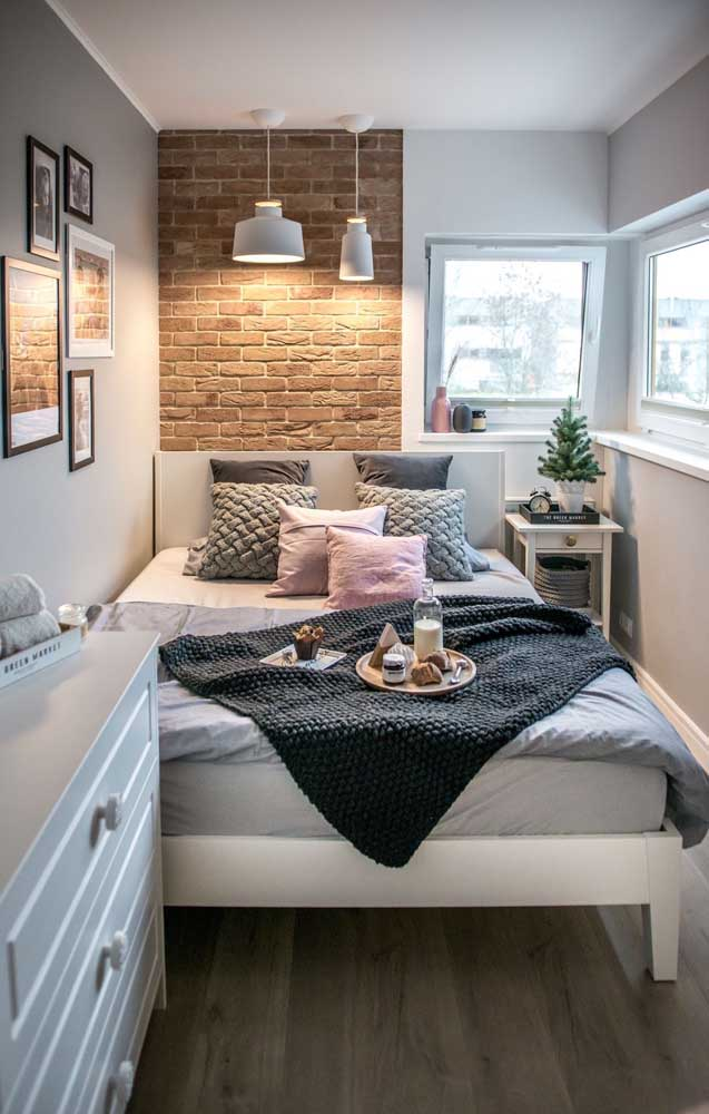 For this super small double room the solution was to lean the bed against the side wall; highlight for the brick covering that gave a touch of warmth in the environment