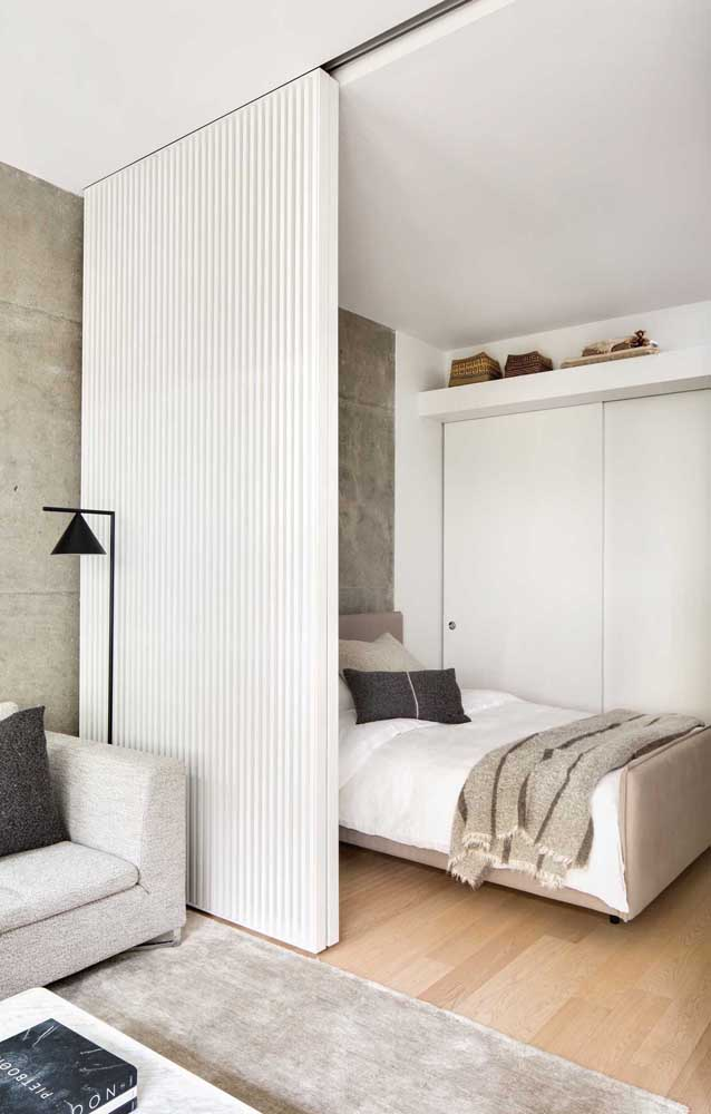 This small double bedroom integrates with the living room; to divide the environments, a sliding wooden panel
