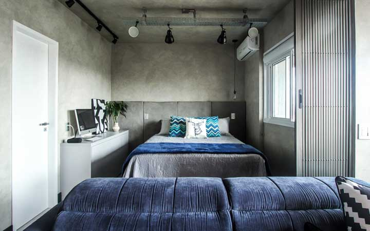 Small industrial style double bedroom has what? Burnt cement on the wall, of course!