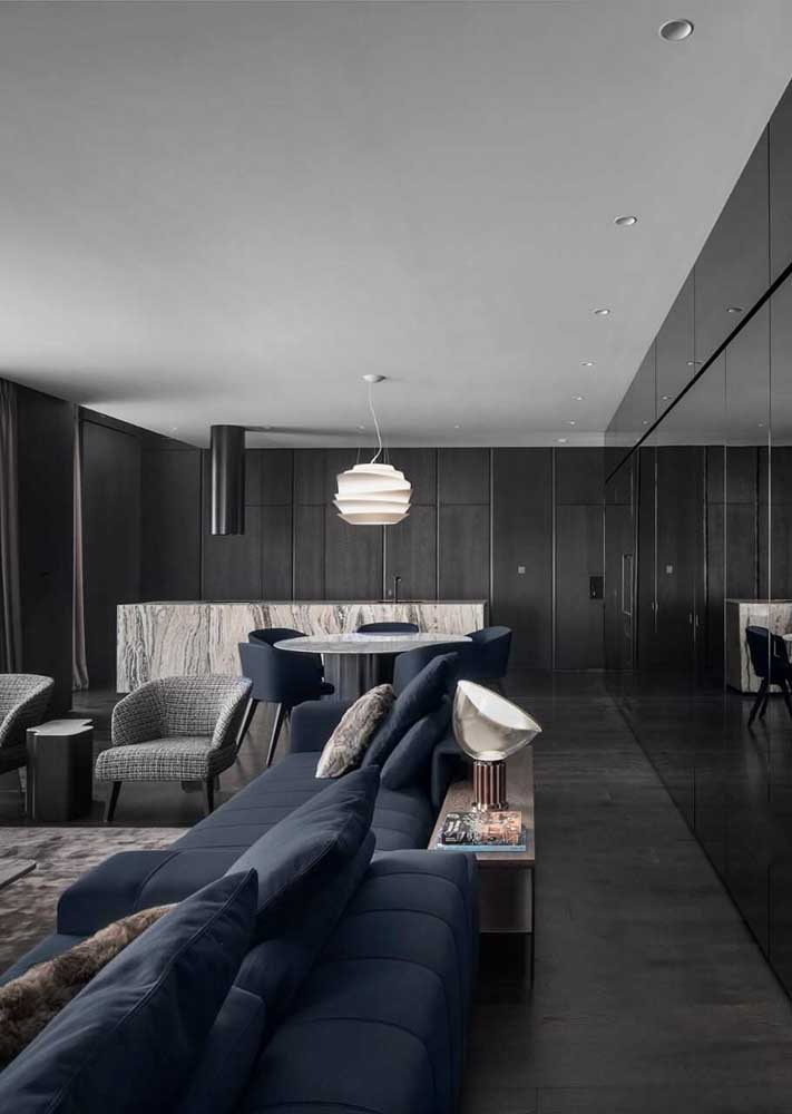 The integrated environment bet on the black floor and walls. The blue sofa breaks the monotony of tones