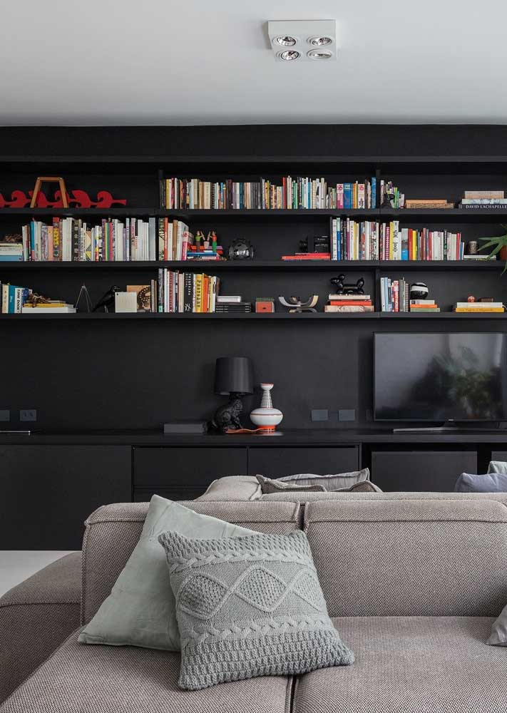 Room with black wall and shelves. Color brings integration to the set