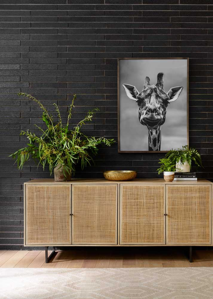 Room with black wall valued for the textures of the furniture and plants