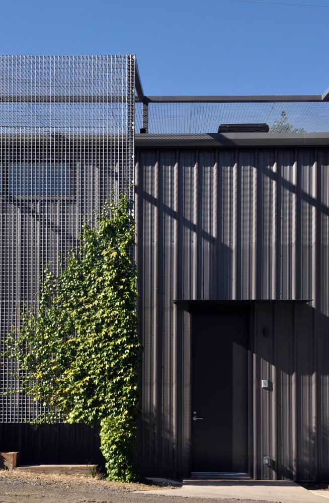 Modern and stylish house facade covered with black sandwich tile and wire screens