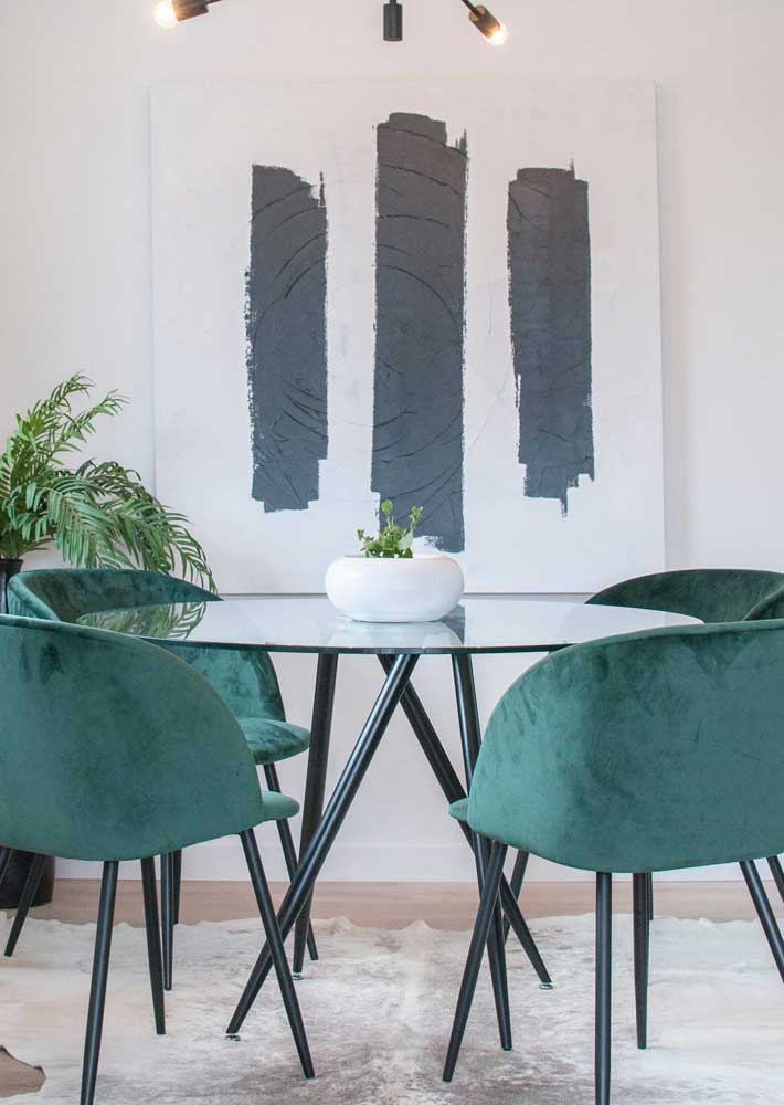 Mesa redonda para sala de jantar complementada pelas modernas cadeiras verdes