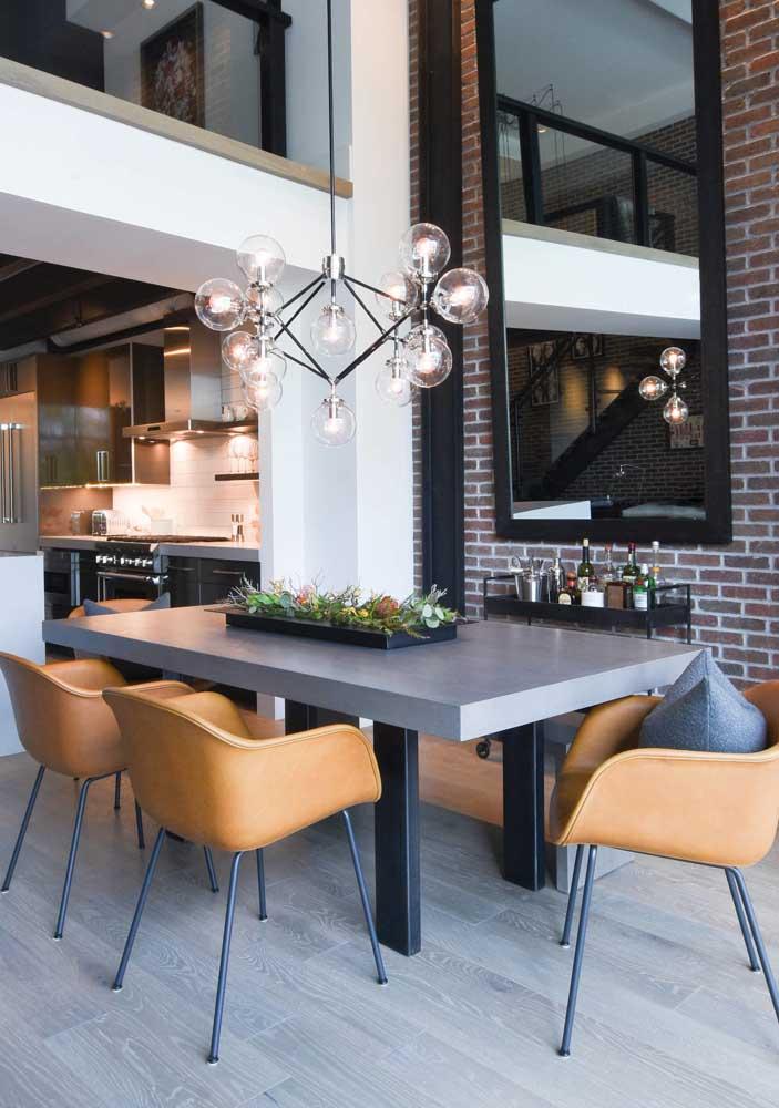 A sala de jantar de pé direito alto ficou mais acolhedora com a luminária pendente sobre a mesa