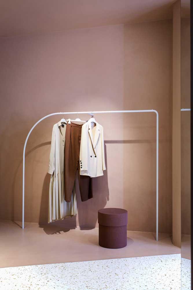 O quarto minimalista apostou no uso de uma arara de roupas clean e de design moderno