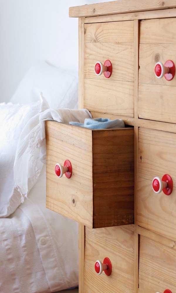 O charme dessa cômoda de madeira são as gavetas pequenininhas e os puxadores vermelhos