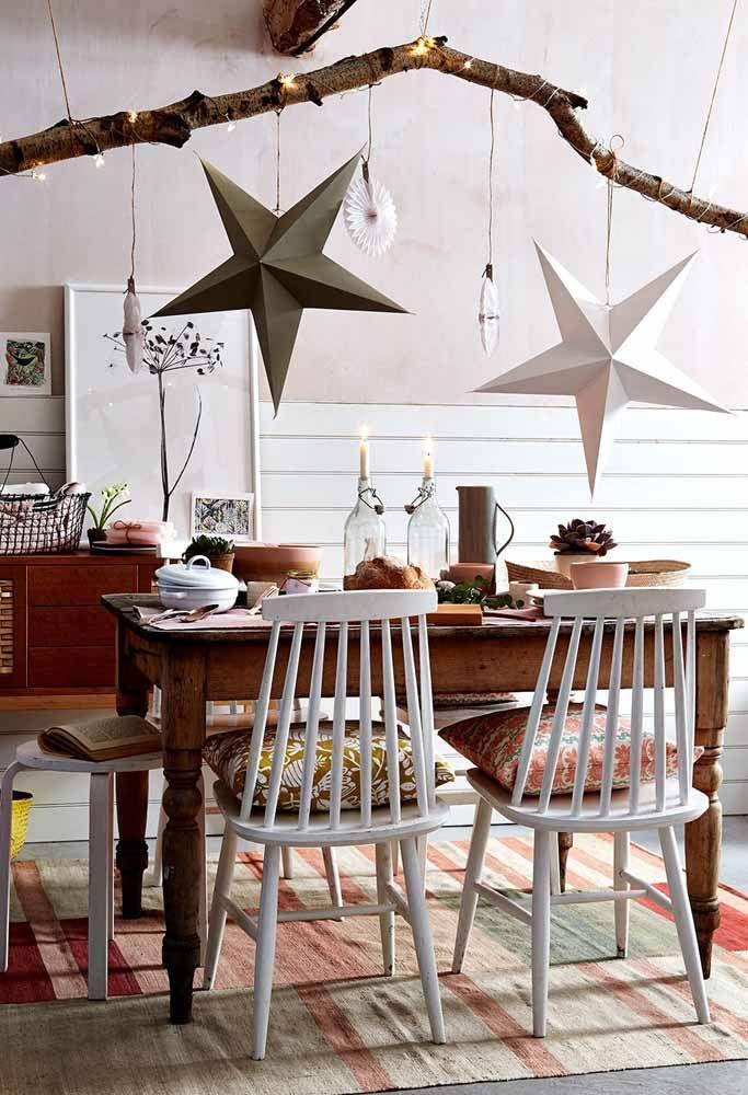 Em um ambiente rústico as estrelas de natal penduradas em um galho fazem toda a diferença na decoração da mesa de natal