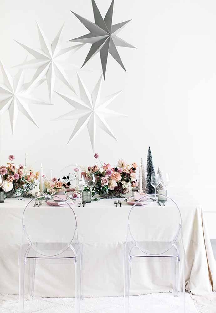 Cadeiras transparentes e a toalha branca para deixar a mesa de natal minimalista e clean