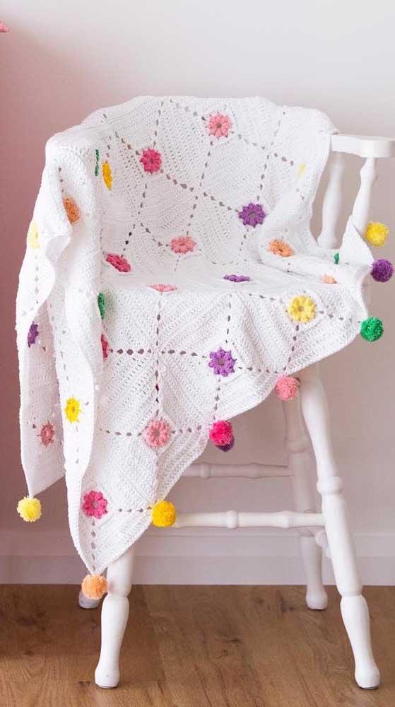 Já aqui, a manta branca de crochê ganhou aplicações de flores também feitas em crochê. Destaque ainda para os pompons que valorizam a peça
