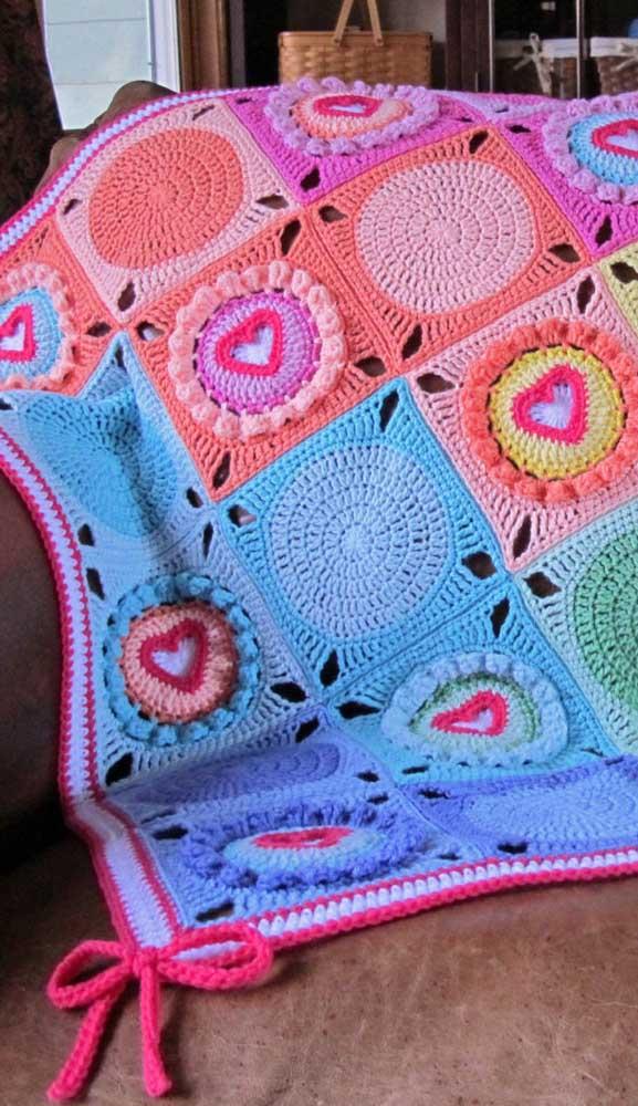 Aqui nessa manta de crochê patchwork foram intercalados círculos e corações. O lacinho finaliza a peça com muita graça