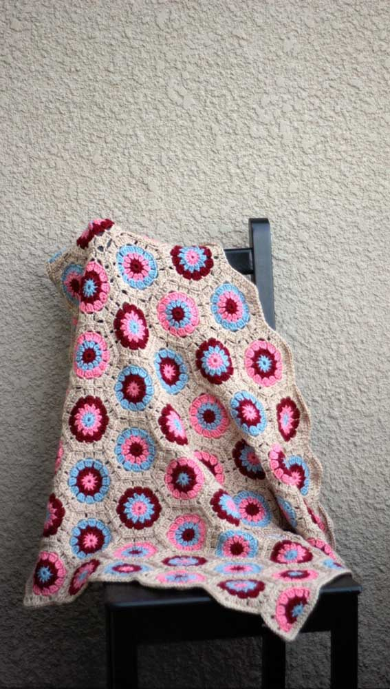 Flores em três tons diferentes colorem essa manta de crochê