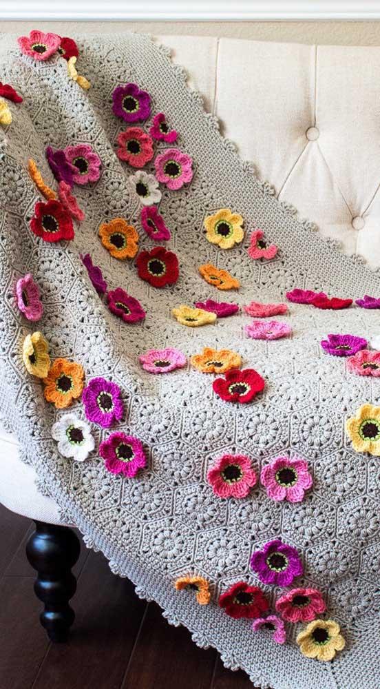 A manta de crochê cinza ganhou aplicações de flores que a deixaram ainda mais incrível