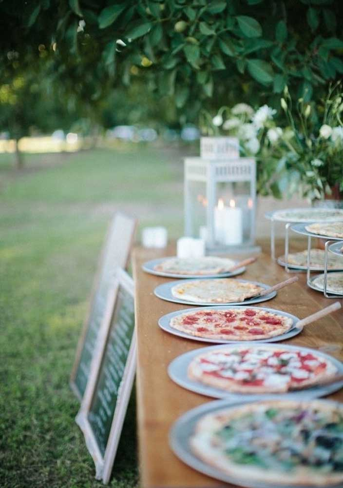 Uma mesa só para as pizzas. O quadro lousa se encarrega de revelar os sabores