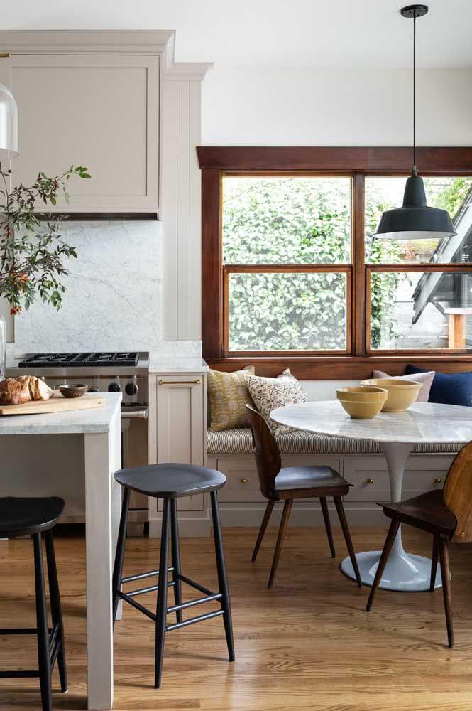 Sala de jantar e cozinha integradas e valorizadas pela janela guilhotina de madeira