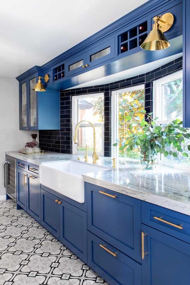 A cozinha azul e preta ganhou luminosidade graças ao trio de janelas guilhotinas próxima da bancada