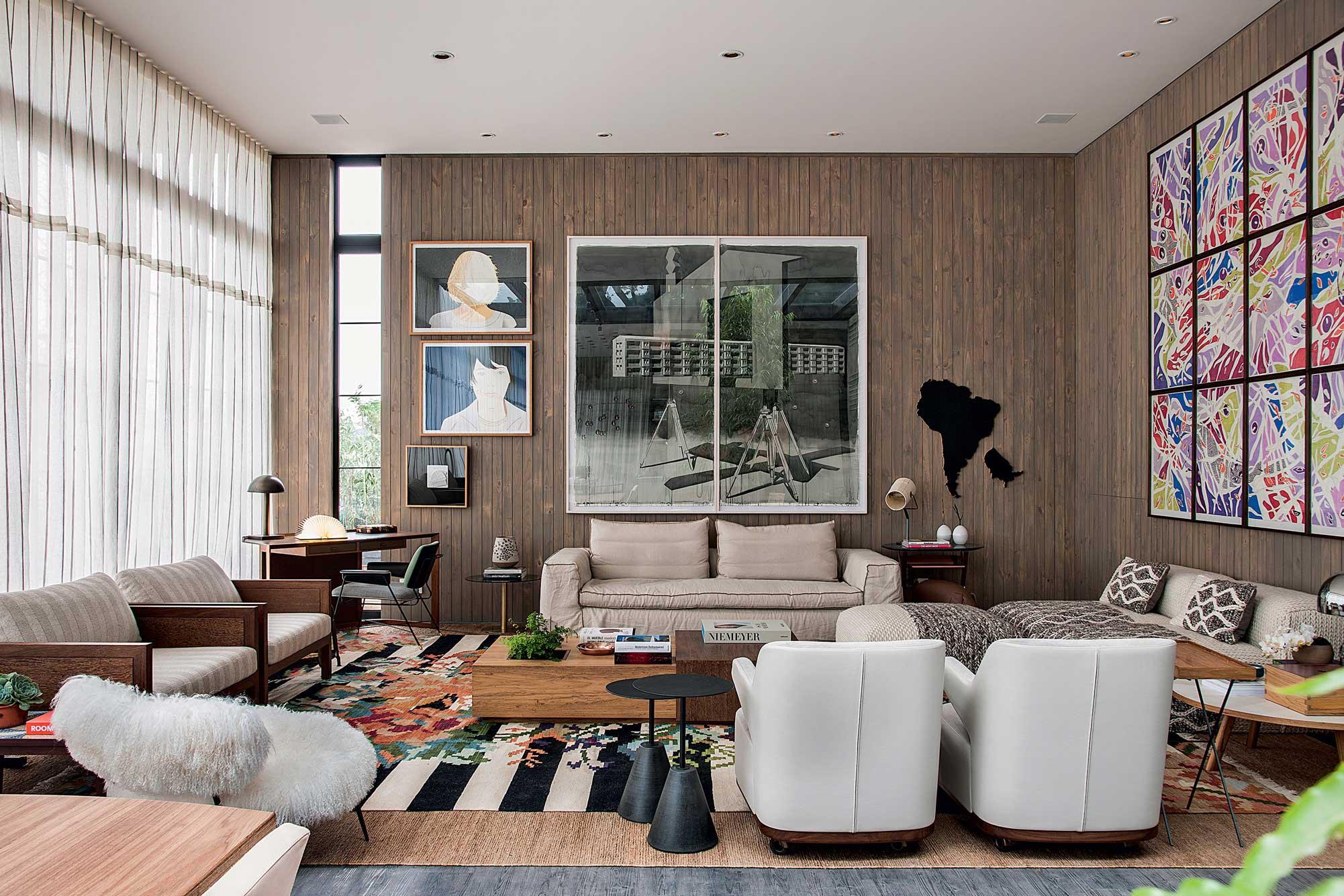 A parede de madeira complementa o visual moderno da sala.