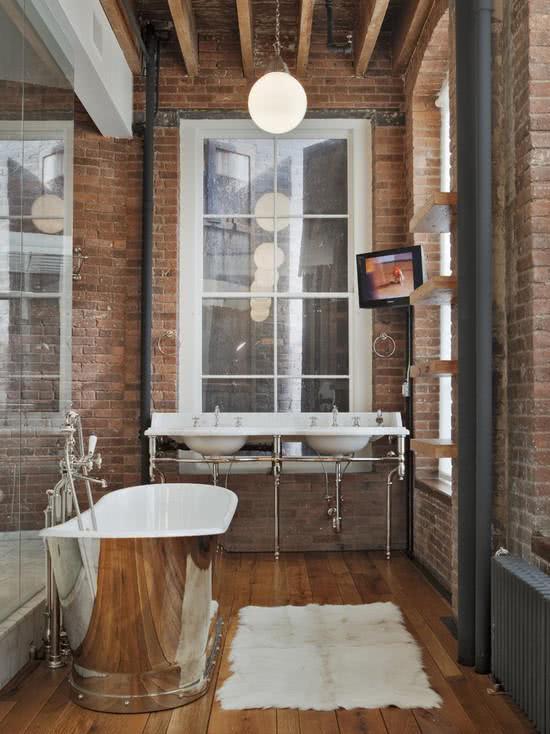 Stainless steel bathtub in a bathroom with bricks