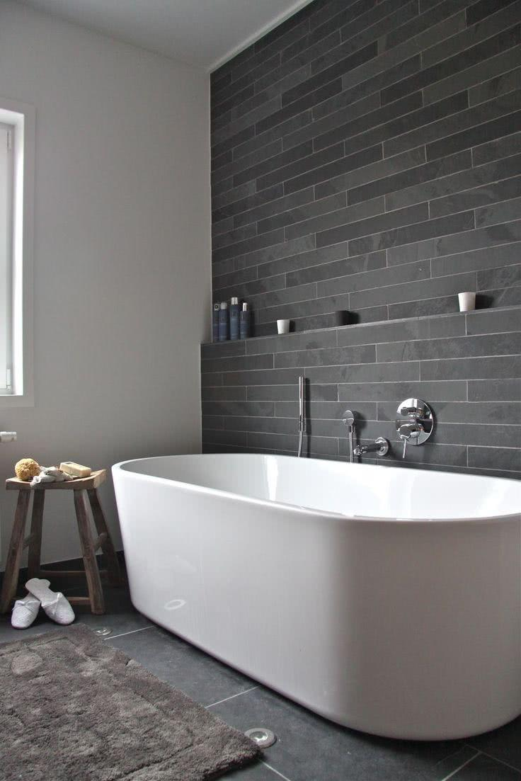 Dark stone wall and simple white bathtub