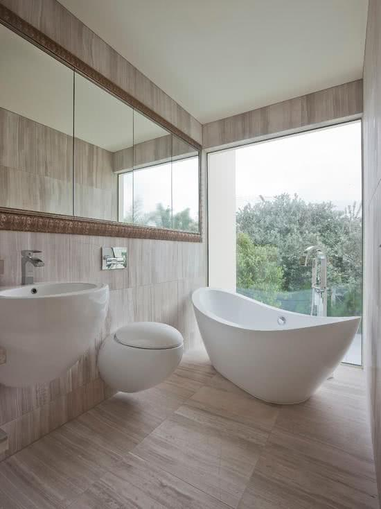 Bathroom with wooden flooring and white bathtub