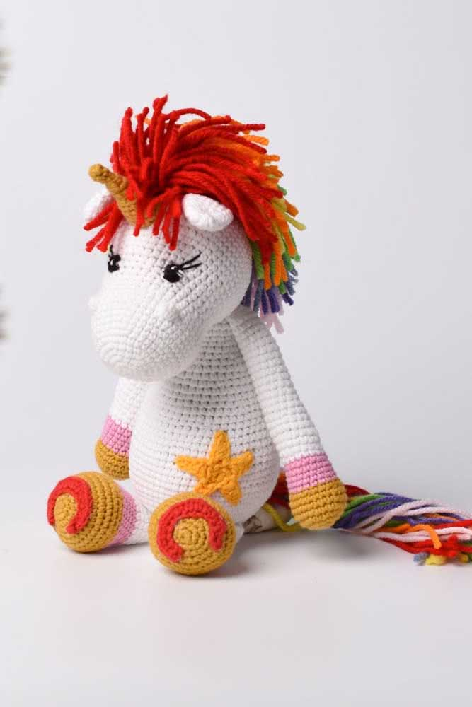 White crochet unicorn with red and orange details to escape the pattern